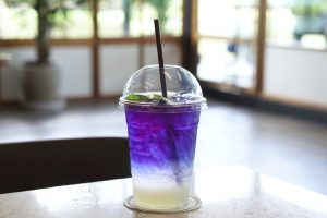 Plastic glass of iced butterfly pea tea with lemon on wooden table, Relax with Thai herbal drink for healthy life in natural concept.